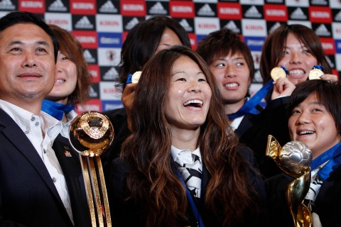 Japan's women's World Cup soccer team head coach Sasaki and players pose during a photo session after a news conference in Tokyo