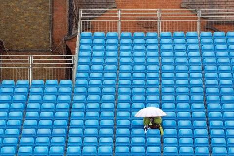A spectator sits in the stands during a rain delay at the Queen's Club Championships in west London