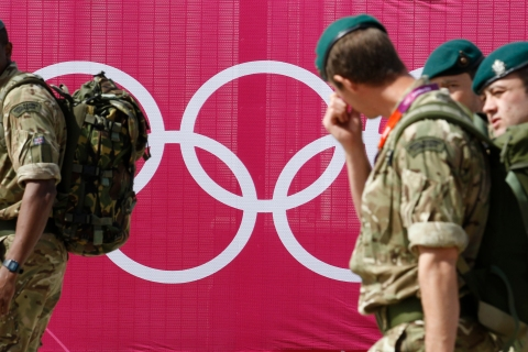 Marines pass the Olympic rings outside the London 2012 Olympic Park at Stratford in London