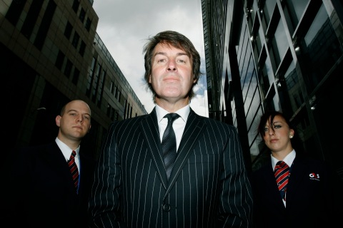 Chief Executive Officer of G4S Buckles  poses with security officers after giving an interview to Reuters in London