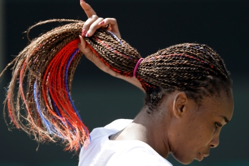 Venus Williams adjusts her hair, which contains red and blue strands, during practice at the All England Lawn Tennis Club at Wimbledon