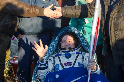 Yurchikhin holds the torch of the 2014 Sochi Winter Olympic Games after landing near the town of Zhezkazgan